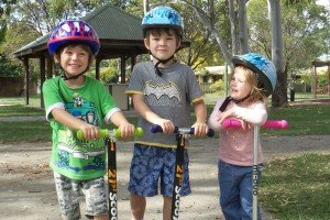 Three kids on scooters after a year in Australia